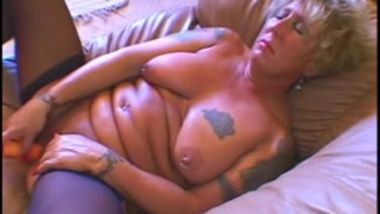 Pierced and tattooed granny masturbating on counch then gets sex.